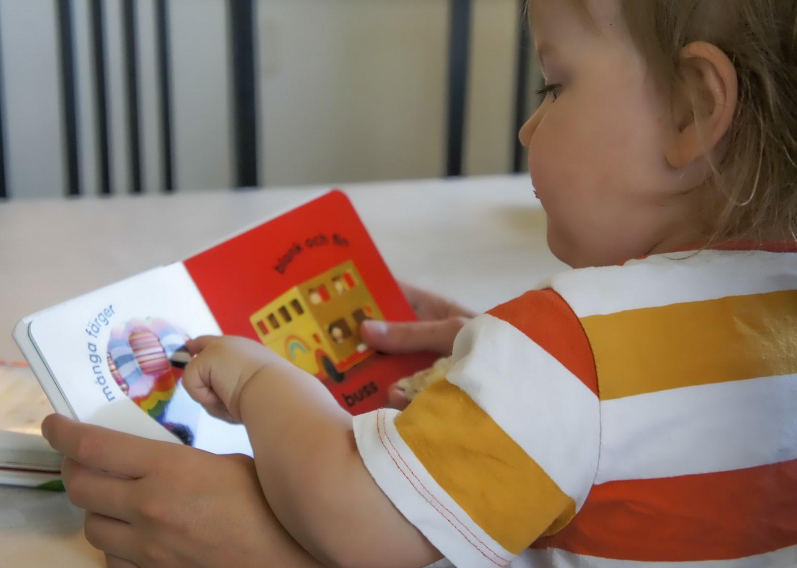 Litet barn läser bok och utveklar sitt språk