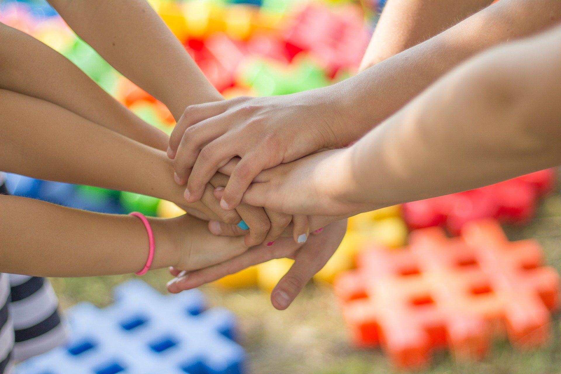 Händer på varandra tillsammans i organiserat team