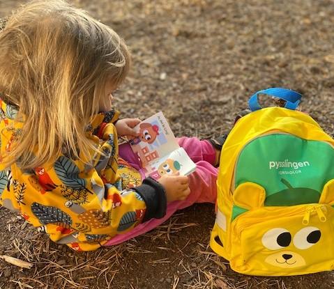 Barn sitter på marken och läser en Pixibok med Pysslingryggsäck bredvid sig