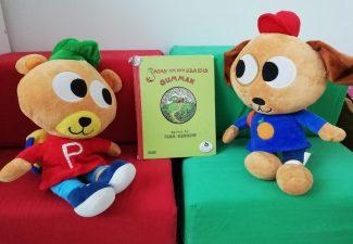 Figurerna Pyss och Ling sitter i en soffa med en sagobok mellan varandra