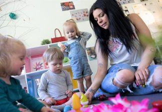 tre barn och pedagog sitter på golv och leker