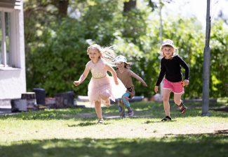 Tre glada flickor i sommarkläder springer på en grön gräsmatta