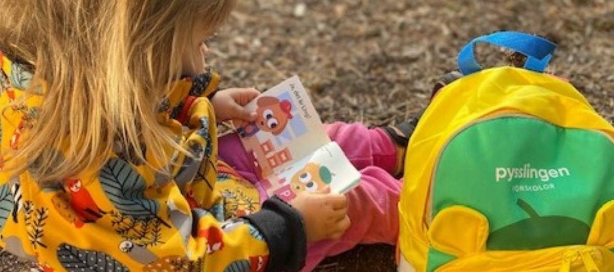flicka läser bok på förskola