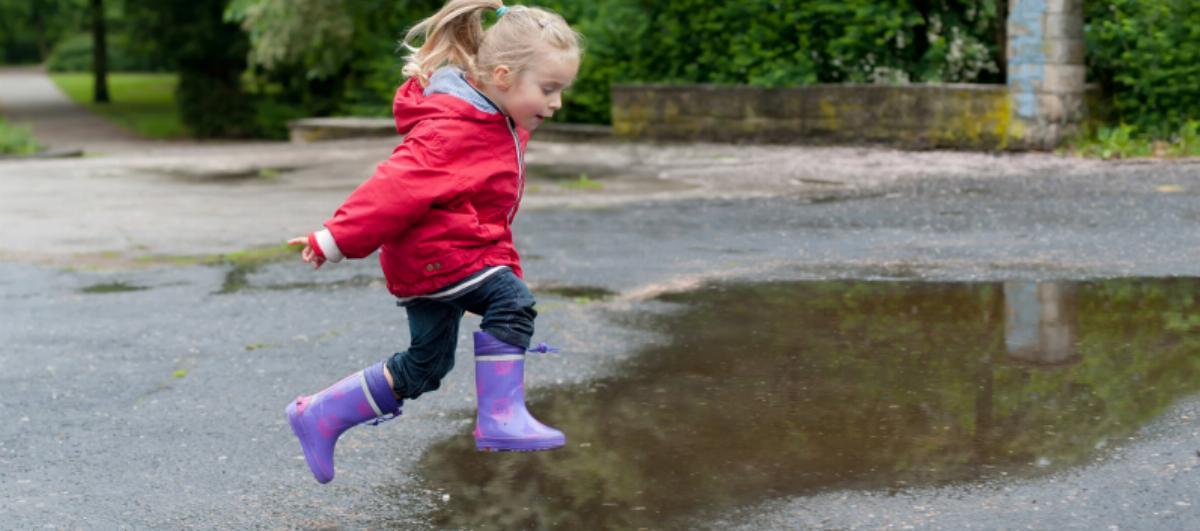Flicka med funktionella kläder och gummistövlar hoppar i vattenpöl