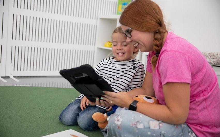 pedagog och barn sitter på golvet och tittar på en ipad