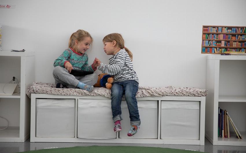 bild av två flickor som sitter på en bänk och pratar inne på förskolan