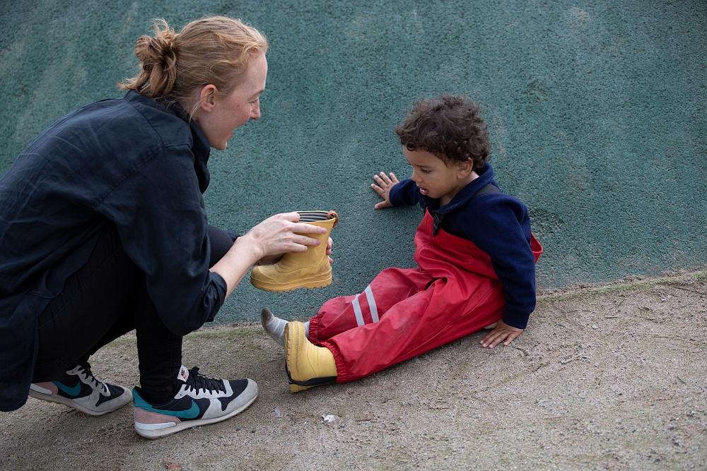 pedagog hjälper barn sätta på stövel pysslingen förskola