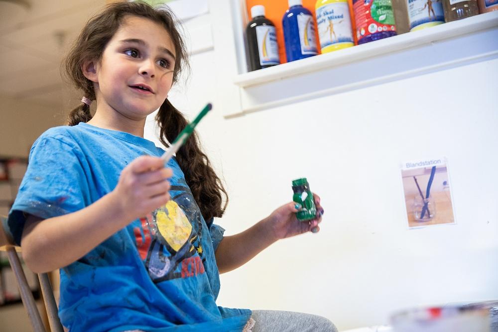 Flicka målar med grön färg på förskola