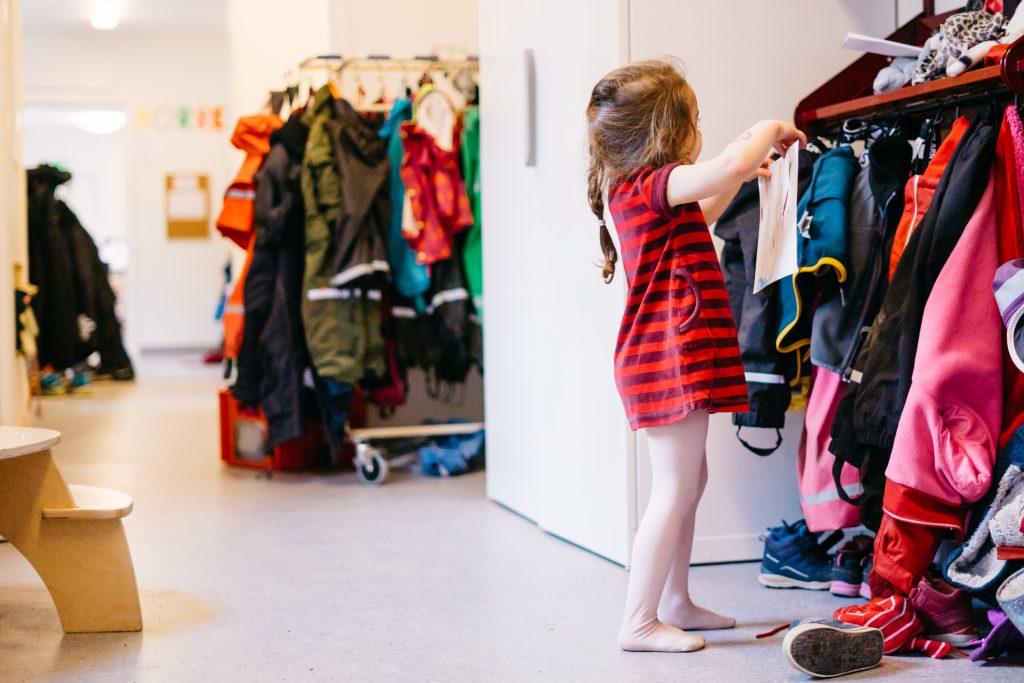 Flicka hänger upp kläder på förskolan