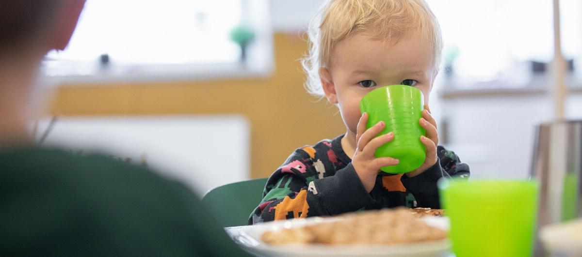Liten pojke dricker på förskola
