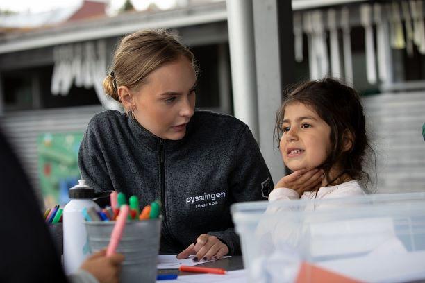 Pedagog lyssnar på ett barn på förskolan