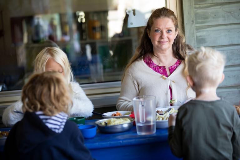 Pedagog på förskola äter med barnen