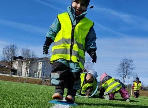 barn som är fysiskt aktiv och går på en linje på en fotbollsplan