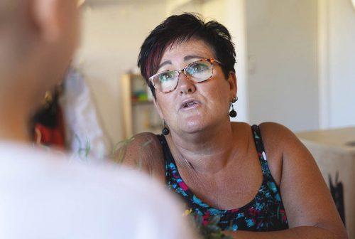 kvinna med glasögon pratar med person vars rygg är vänd mot kameran