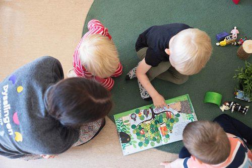 barn och pedagog sitter på golvet och läser en bok tillsammans
